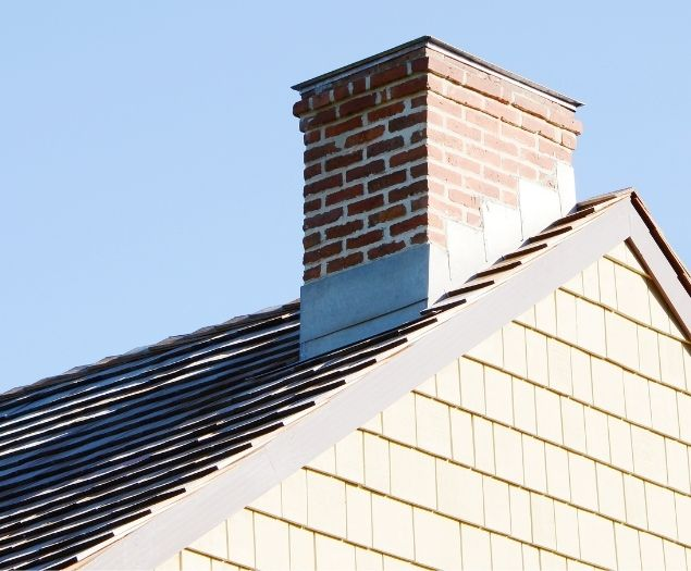 A short brick chimney on the roof of a residential home