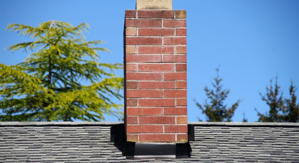 A brick chimney on the roof of a residential home