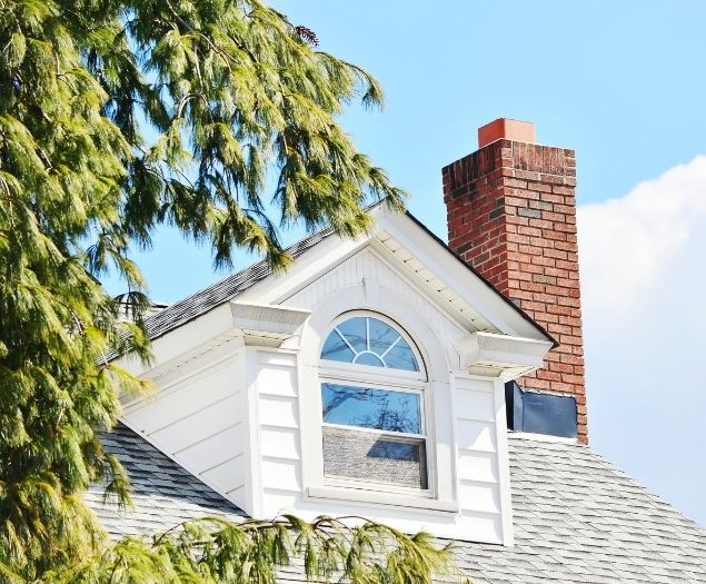 A tall brick chimney installed on the roof of a residential home