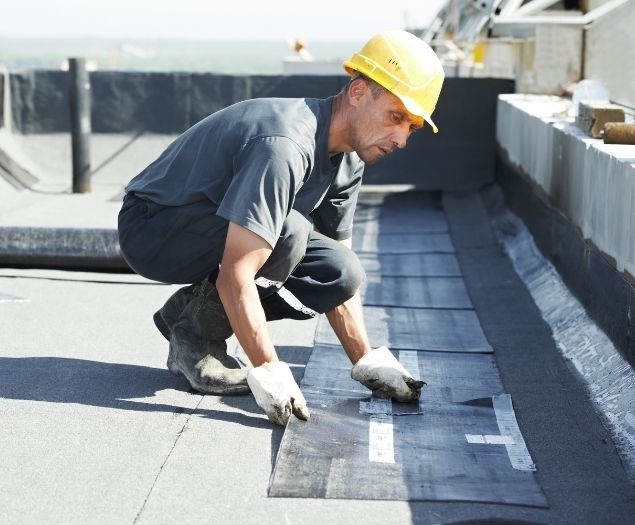 A roofer laying down a commercial shingle roof