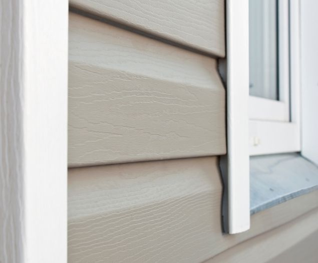 Tan siding installed on the side of a residential home