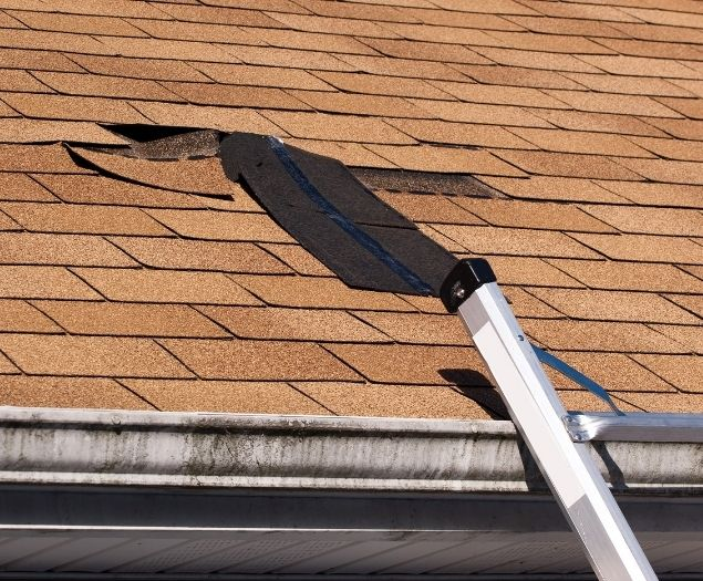 Damaged shingles on the roof of a residential home