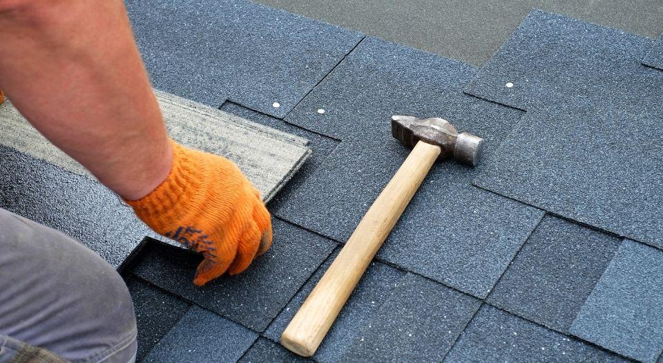 A man installing a black shingle roof.