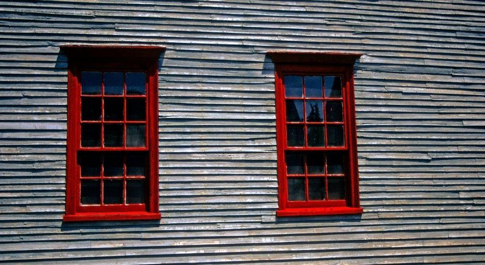 Tan siding surrounding two red windows.
