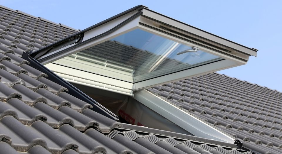 A open skylight in the roof of a residential home.